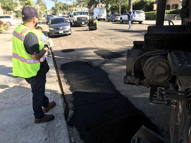 City employees filling a pothole in the University Heights neighborhood on Oc...