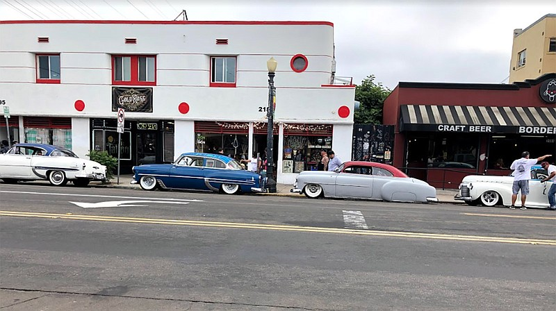 A line of lowriders parked on Logan Avenue in Barrio Logan for the La Vuelta ...