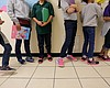Migrant teens line up for a class at a