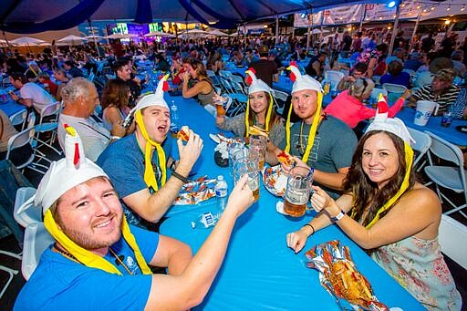 People with chicken hats, cheering and eating at the La Mesa Oktoberfest in t...