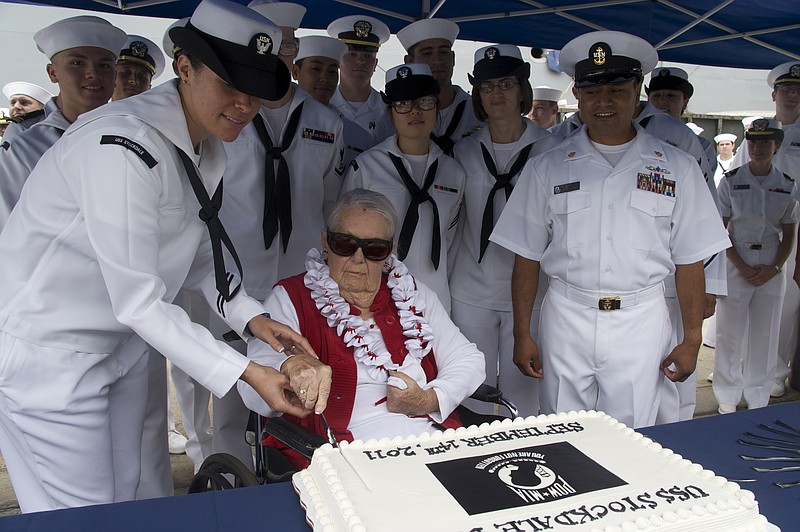 Sybil Stockdale, widow of Adm. James B. Stockdale, cuts a cake during a cerem...