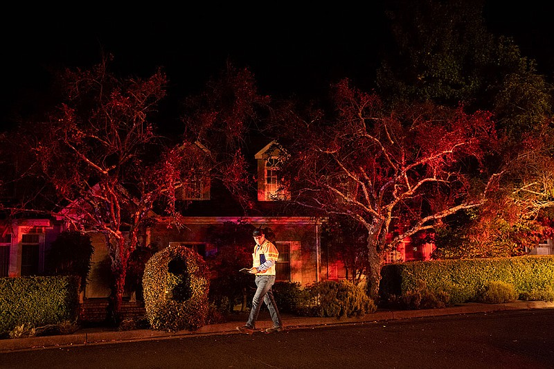 A Pacific Gas & Electric worker passes a home on Merrill Dr. in Moraga, Calif...