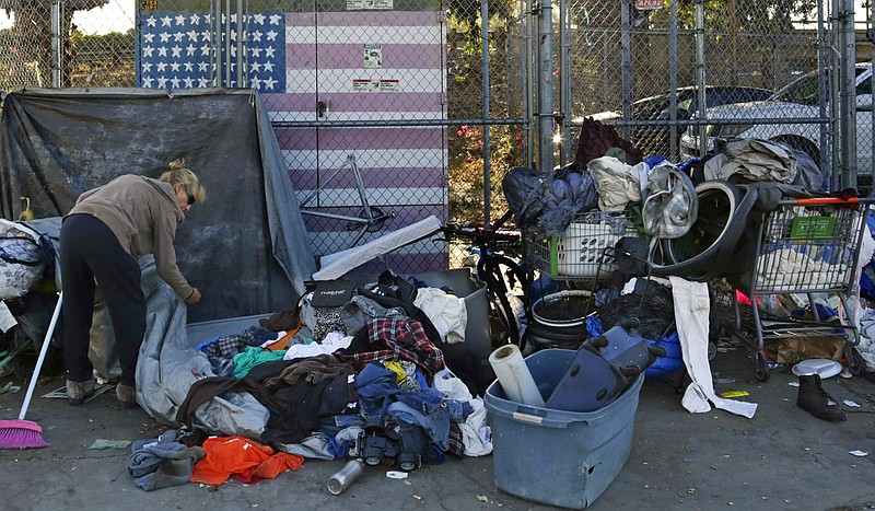 A homeless woman who was camping in downtown San Diego sorts through her belo...