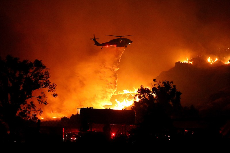 Water is dropped on a large brush fire Friday, Oct. 11, 2019, in Sylmar, Calif.