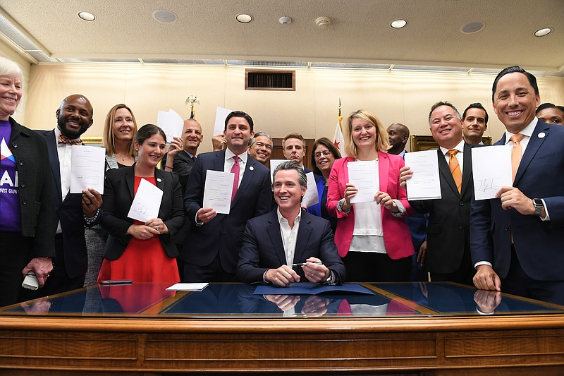 California Gov. Gavin Newsom, seated with several Assembly members holding a ...