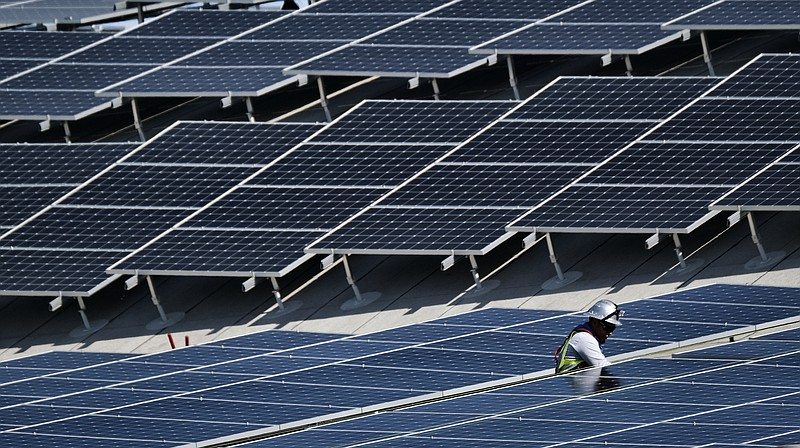 A worker helps to install solar panels onto a roof in the Van Nuys section of...