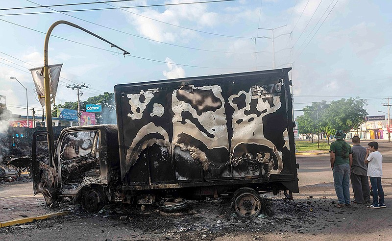 A burnt out truck used by gunmen smoldering on an intersection, a day after s...