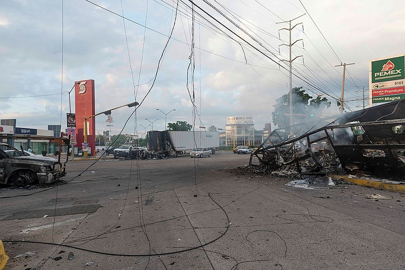 Burnt out vehicles used by gunmen smolder on an intersection, a day after str...