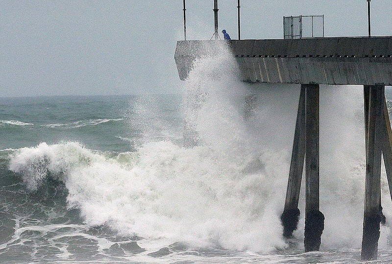 A man stands near crashing waves on the Pacifica Pier in Pacifica, Calif., Tu...