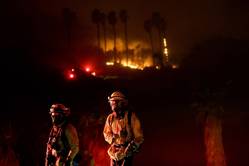 Fire crews look on as they fight a wildfire Thursday, Dec. 7, 2017, in Bonsal...