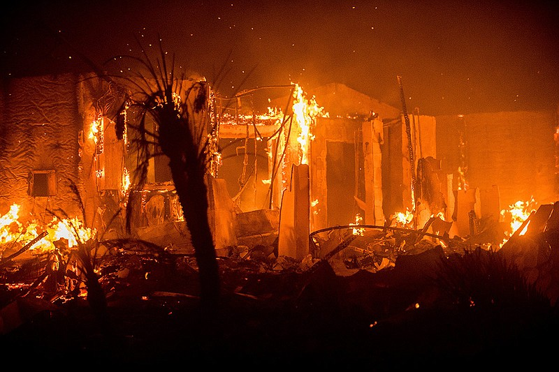 Flames consume a structure as the Lilac fire burns in Bonsall, Calif., on Fri...