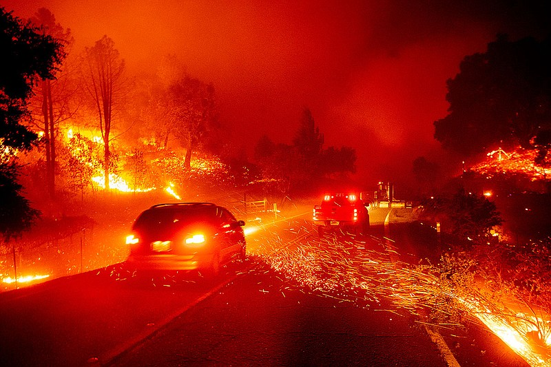 Embers fly across a roadway as the Kincade Fire burns through the Jimtown com...