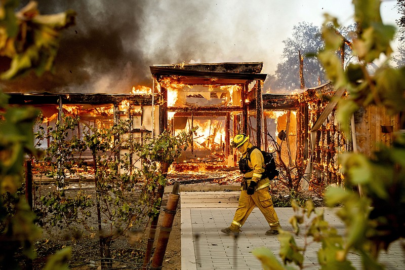 Woodbridge firefighter Joe Zurilgen passes a burning home as the Kincade Fire...