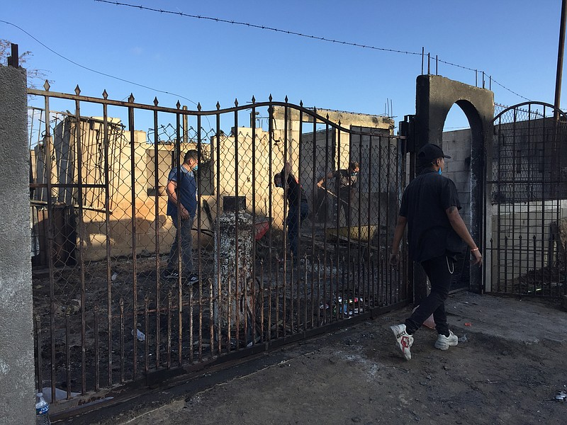 Volunteers clear ash from a burnt-out home in the Morelos neighborhood of Ros...
