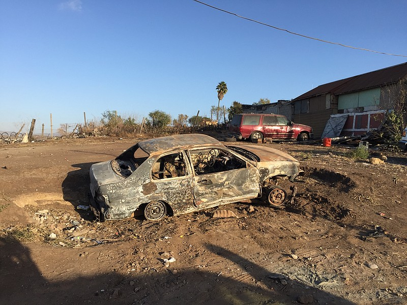 A burned-out car in the Morelos neighborhood of Rosarito, Mexico on Oct. 29, ...