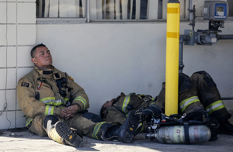 Firefighters rest at outside a cardboard box factory that burned down by a wi...