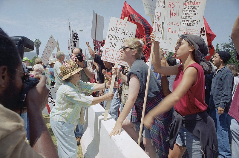 Pro Prop. 187 demonstrator Catherine Nicosia, 74, left, tries to take signs o...
