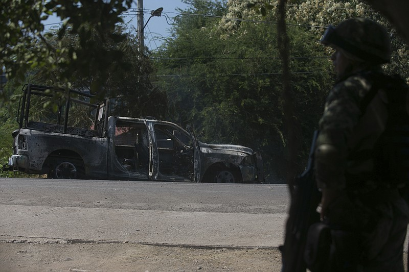 A soldier stands by a charred truck that belongs to Michoacan state police, a...