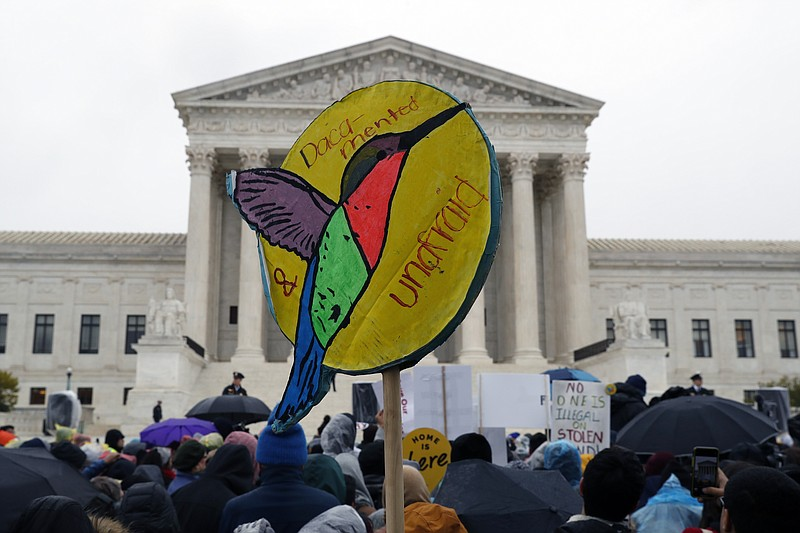 People rally outside the Supreme Court as oral arguments are heard in the cas...