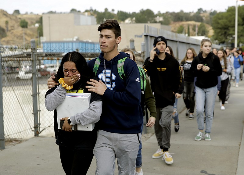 Students are escorted out of Saugus High School after a shooting on Thursday,...