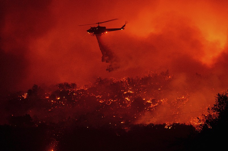 A helicopter drops water on the Cave Fire burning along Highway 154 in Los Pa...