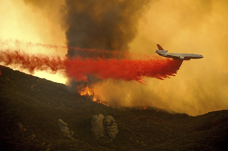 A DC-10 air tanker drops retardant to slow the Cave Fire burning in Los Padre...