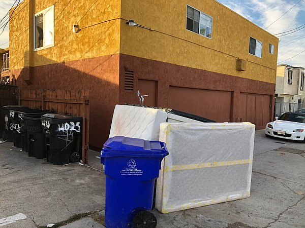 Two discarded mattresses sit next to a recycle bin in a C...