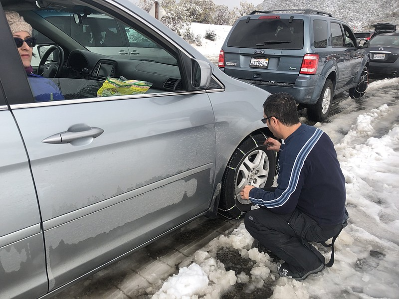 A man putting on chains on Sunrise Highway before heading to Mount Laguna on ...