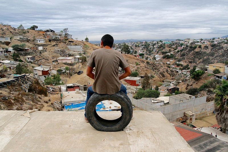 In this undated photo, a volunteer sits on one of the dozens of old tires use...