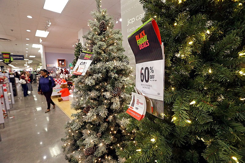 A shopper walks past a display of artificial Christmas trees at a JCPenney st...