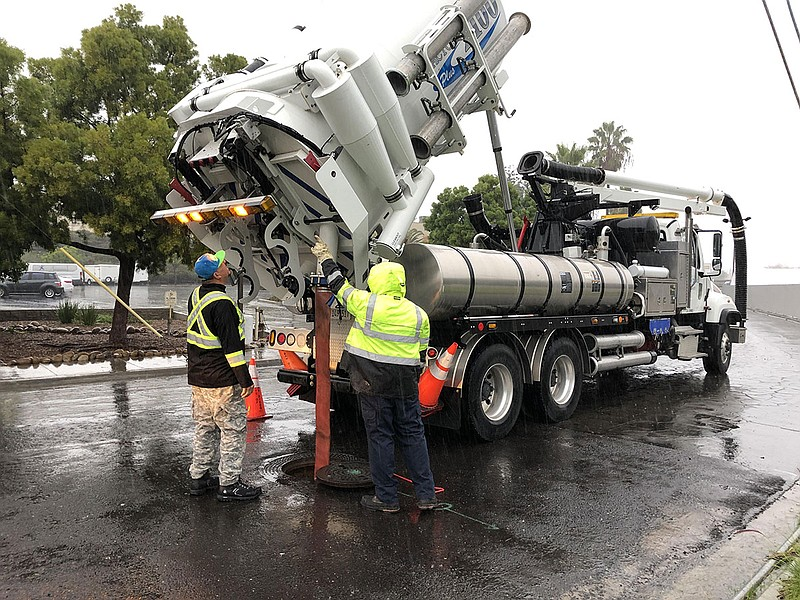 City workers pump sewers during a rainstorm in order to prevent flooding in S...