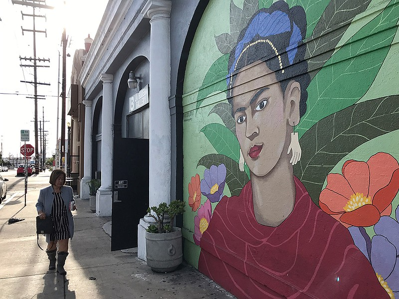 A woman walks in front of the La Bodega Gallery in Barrio Logan, Dec. 5, 2019.