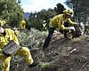 A fire prevention crew hauls away sections of a...