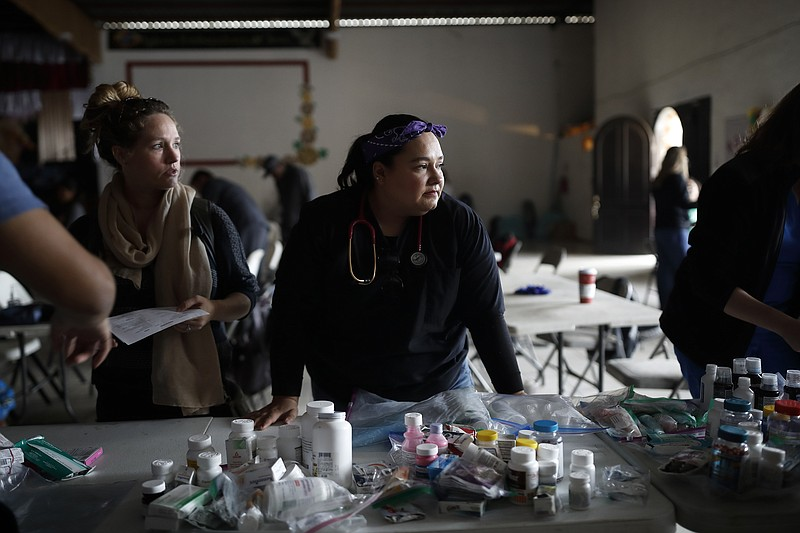 Psyche Calderon, center, pauses for a moment as she works alongside other vol...