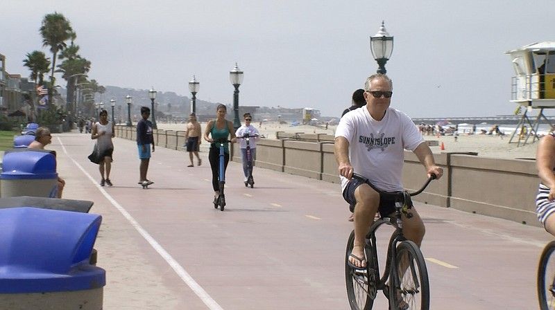 People riding scooters and bicycles on the Mission Beach Boardwalk on July 29...