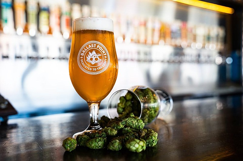 A glass of Ballast Point beer next to some hops in this undated photo.