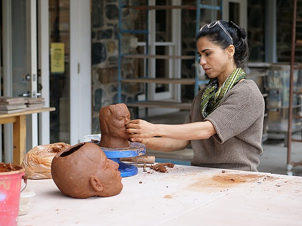 Cristina Córdova sculpting a head out of clay.