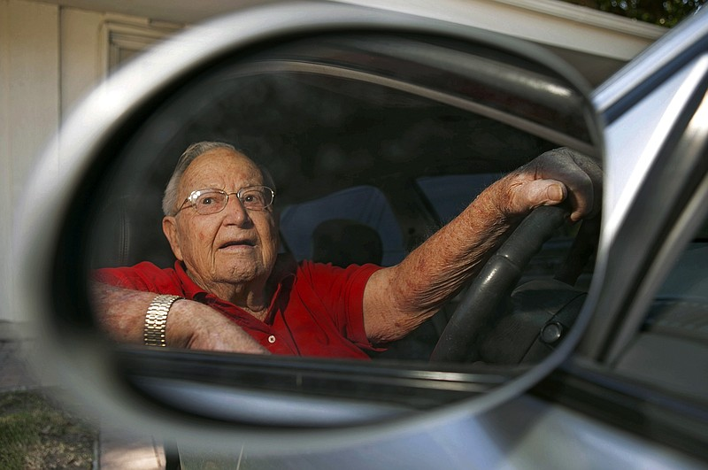 Jack Wyrad, 92, is seen reflected on his side mirrors as he adjusts them befo...