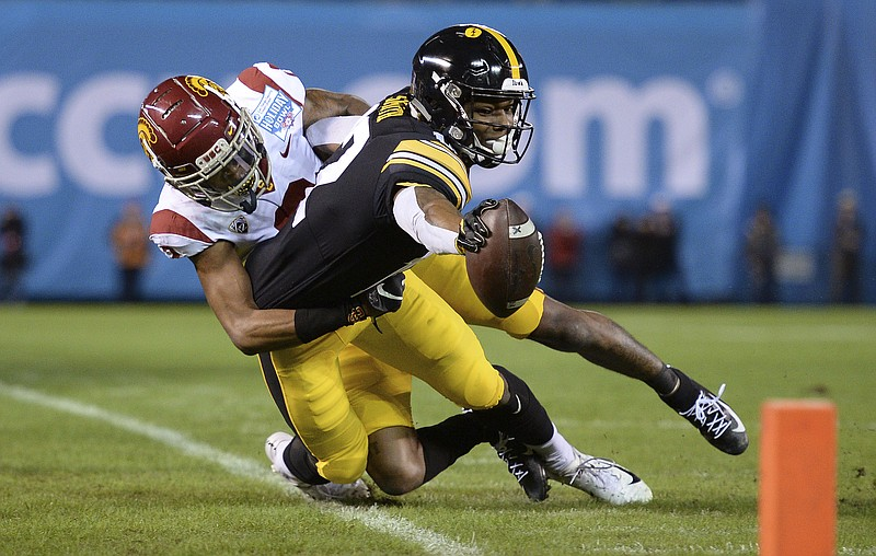 Iowa wide receiver Brandon Smith, right, reaches forward as he goes out of bo...