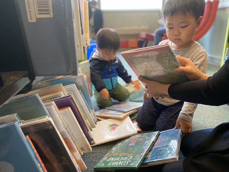 Four-year-old Patrick Jang looks down at a picture book that his mother is ho...