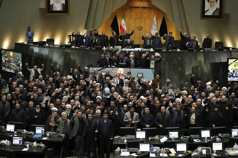 Iranian lawmakers chant slogans as some of them hold posters of Gen. Qassem S...
