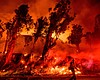 Flames from a backfire consume a hillside as fi...