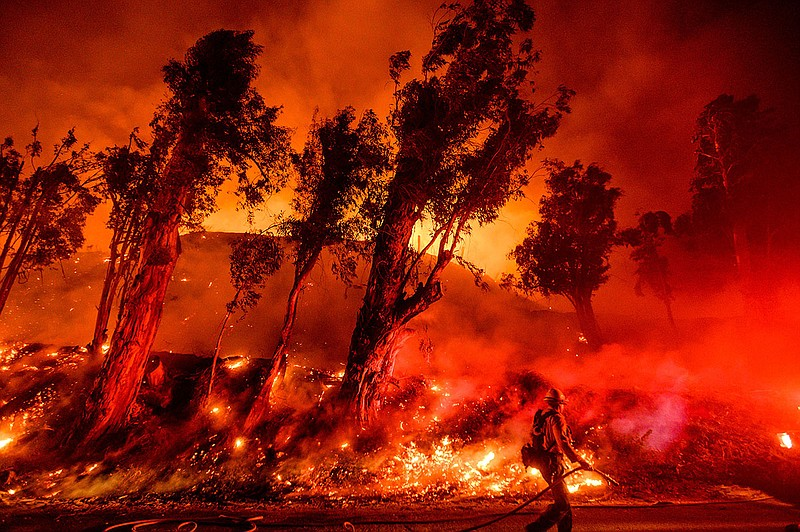 Flames from a backfire consume a hillside as firefighters battle the Maria Fi...