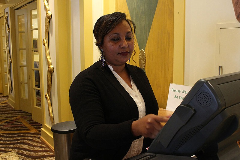 Eden Asfaha, an asylee from Eritrea, works the cashier at a Holiday Inn resta...