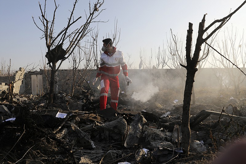 A rescue worker searches the scene where an Ukrainian plane crashed in Shahed...