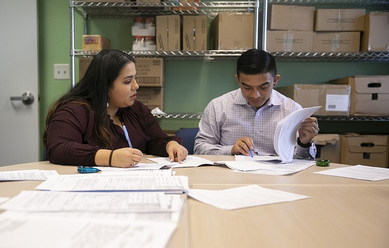 Volunteer Daniella Martinez, left, and Shane Sagisi, a law clerk with San Mat...