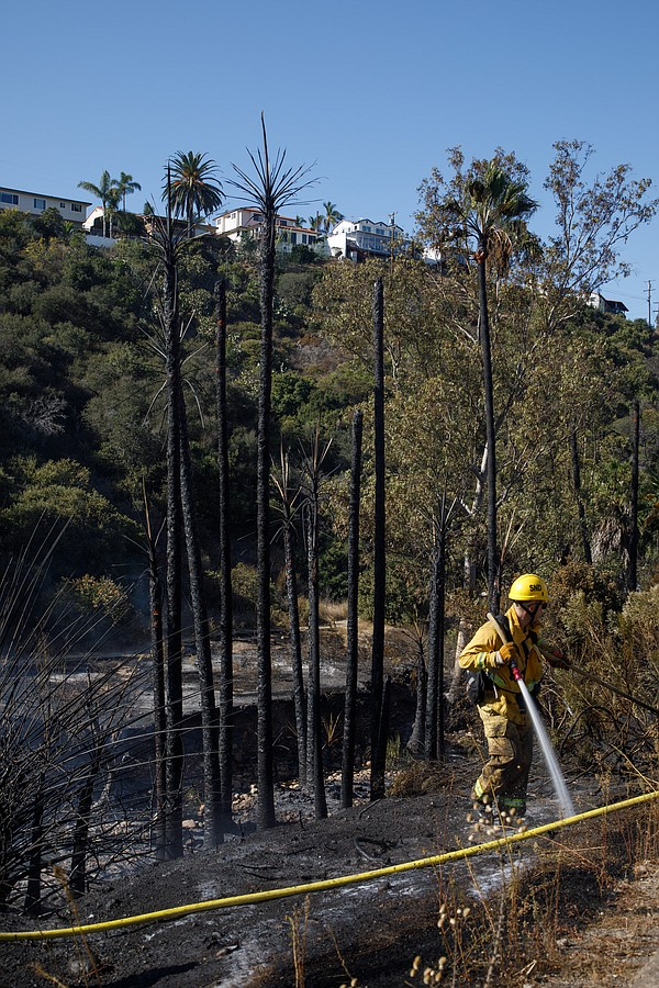 A San Diego firefighter works to mop up a fire near Fairm...