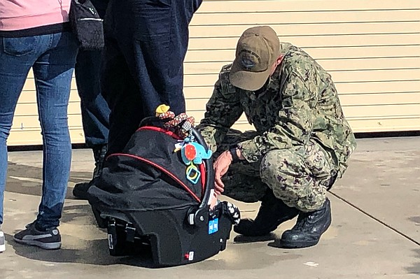 A sailor saying goodbye to his baby before being deployed...
