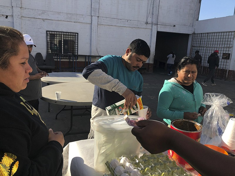 Joel Caceres, center, pours milk in his coffee as other asylum seekers at a m...