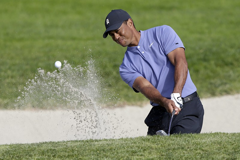 Tiger Woods plays a shot from a bunker on the eighth hole of the Torrey Pines...